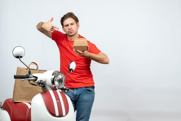 Vue de face du livreur surpris en uniforme rouge debout près de scooter pointant petite boîte sur fond blanc