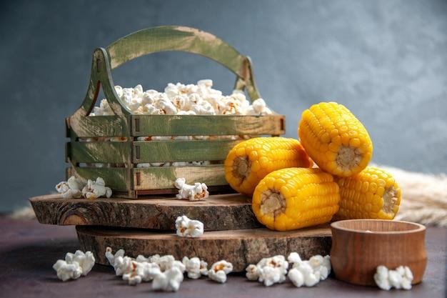 Vue de face du maïs soufflé frais avec des cors jaunes sur un bureau sombre
