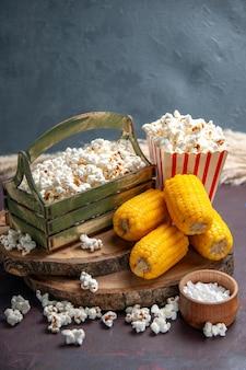 Vue de face du maïs soufflé frais avec des cors jaunes sur la surface sombre du maïs soufflé à la surface