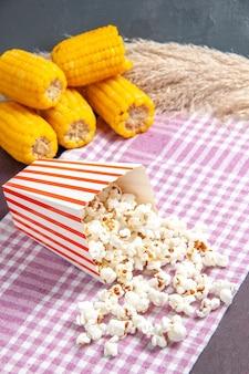 Vue de face du maïs soufflé frais avec des cors jaunes sur la surface sombre du maïs soufflé