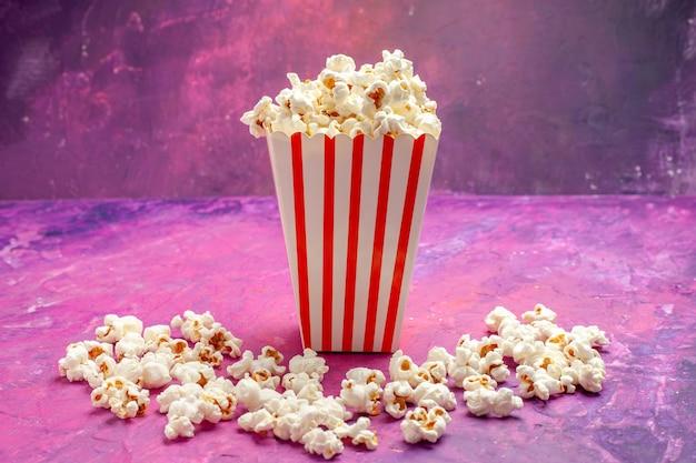 Vue de face du maïs soufflé frais sur la couleur de cinéma de film de table rose
