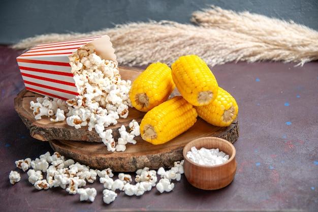 Vue de face du maïs soufflé frais avec des grains de maïs tranchés jaunes sur la surface sombre du maïs soufflé