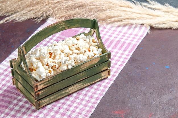 Vue de face du maïs soufflé frais à l'intérieur d'une boîte en bois sur du maïs soufflé à la surface sombre
