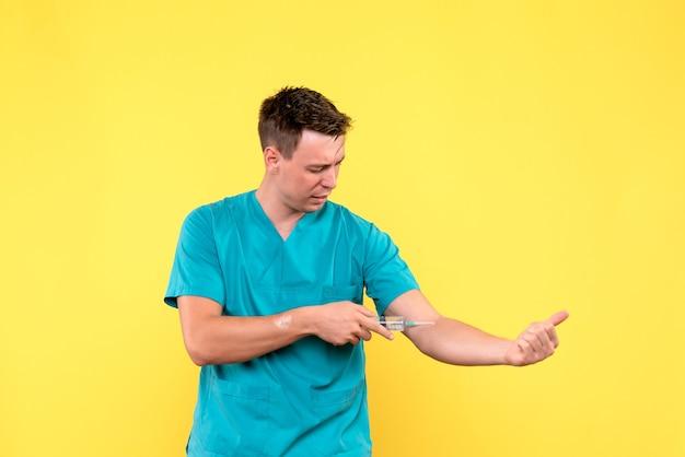 Vue de face du médecin à l'aide d'une énorme injection sur mur jaune