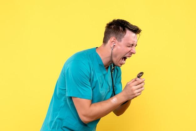 Vue de face du médecin crier au tonomètre sur mur jaune