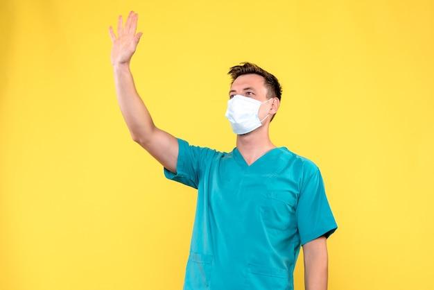 Vue de face du médecin de sexe masculin en agitant à quelqu'un sur le mur jaune