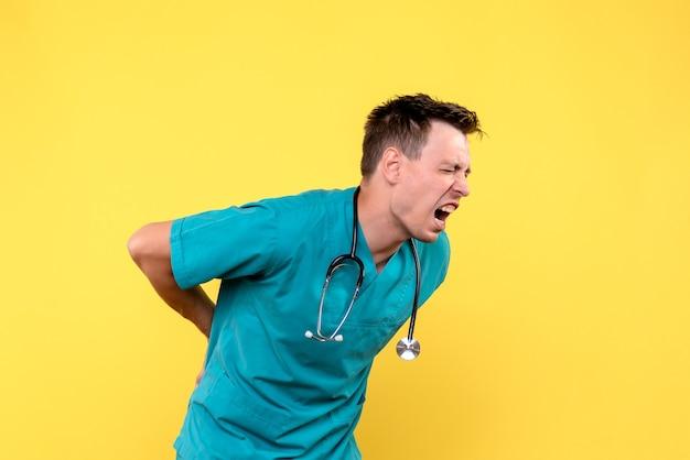 Vue de face du médecin de sexe masculin ayant mal au dos sur mur jaune