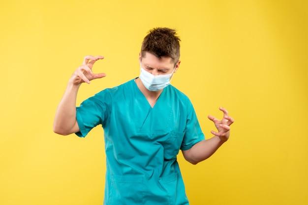 Vue de face du médecin de sexe masculin en costume médical et masque stérile sur mur jaune