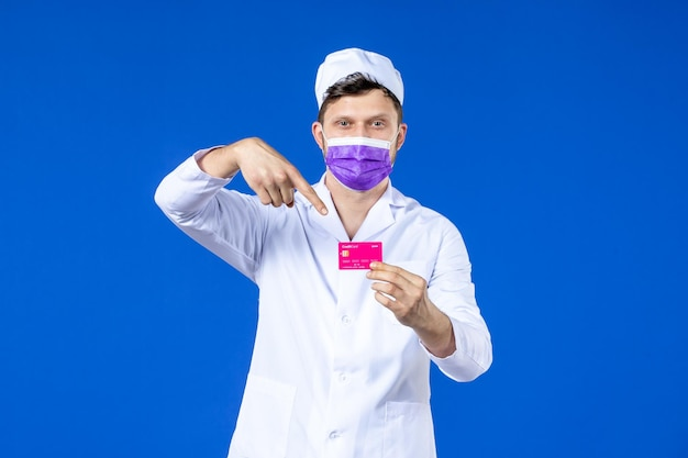 Vue de face du médecin de sexe masculin en costume médical et masque tenant une carte de crédit sur bleu