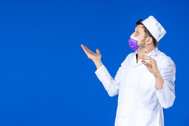 Vue de face du médecin de sexe masculin en costume médical et masque tenant l'injection sur bleu