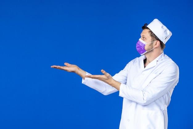 Vue de face du médecin de sexe masculin en costume médical et masque violet sur bleu