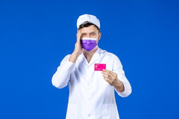 Vue de face du médecin de sexe masculin en costume médical et masque violet tenant la carte de crédit sur bleu