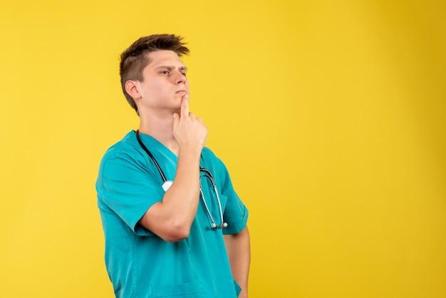 Vue de face du médecin de sexe masculin en costume médical avec stéthoscope sur mur jaune