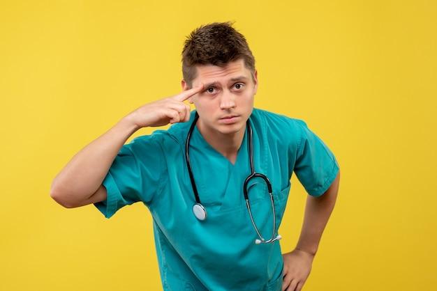 Vue de face du médecin de sexe masculin en costume médical avec stéthoscope sur son cou sur mur jaune