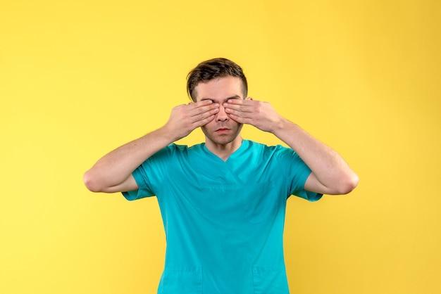 Vue de face du médecin de sexe masculin couvrant ses yeux sur le mur jaune