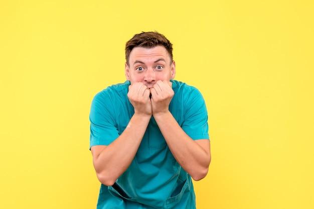 Vue de face du médecin de sexe masculin avec expression nerveuse sur mur jaune
