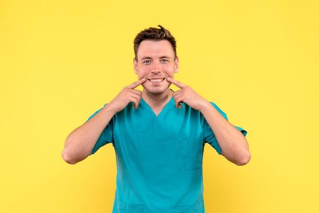 Vue de face du médecin de sexe masculin avec une expression souriante sur le mur jaune