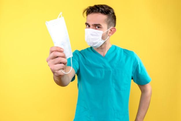 Vue de face du médecin de sexe masculin avec masque sur mur jaune