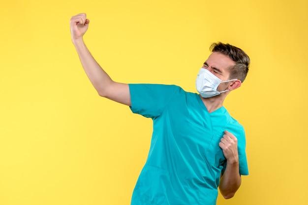 Vue de face du médecin de sexe masculin avec masque stérile sur mur jaune