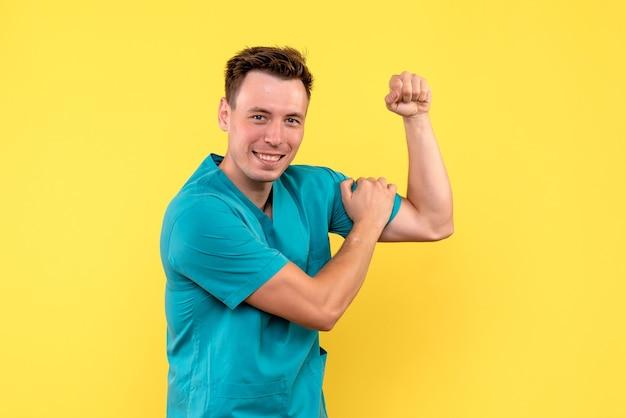 Vue de face du médecin de sexe masculin sur mur jaune
