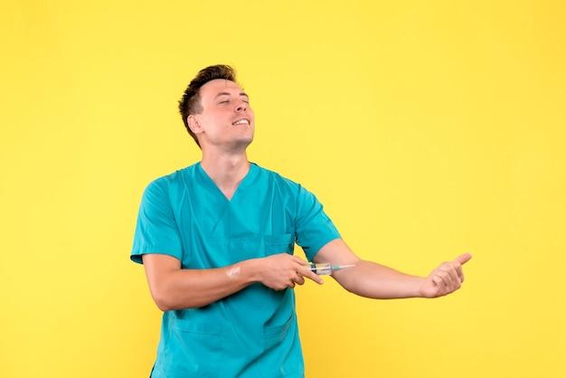 Vue de face du médecin de sexe masculin s'injectant sur mur jaune