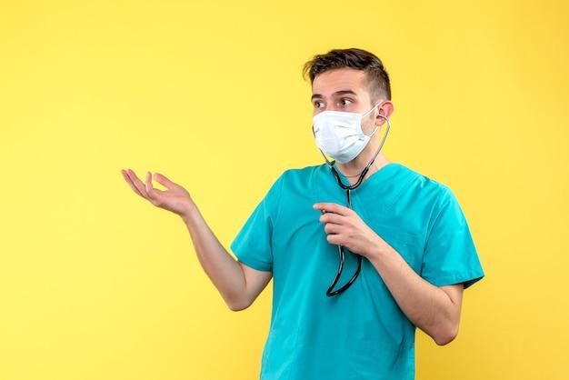 Vue de face du médecin de sexe masculin avec stéthoscope et masque sur mur jaune