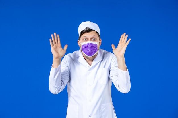 Vue de face du médecin de sexe masculin surpris en costume médical et masque violet sur bleu