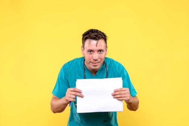 Vue de face du médecin de sexe masculin tenant des fichiers papier sur mur jaune