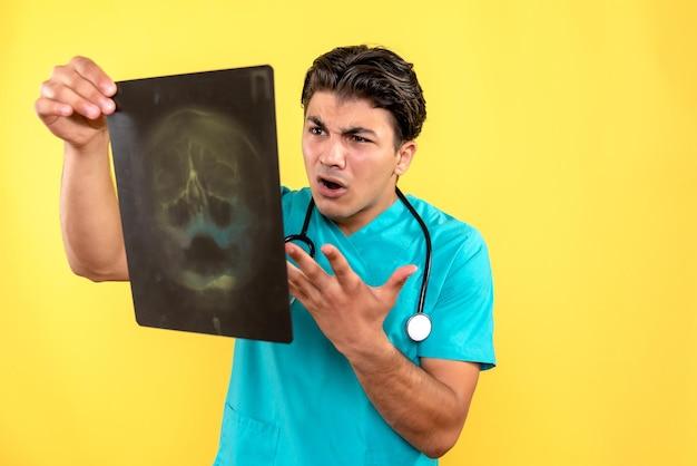 Vue de face du médecin de sexe masculin tenant une radiographie
