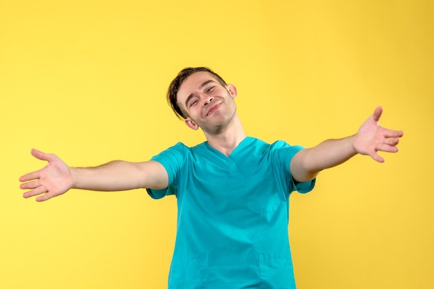 Vue de face du médecin de sexe masculin avec visage ravi sur mur jaune