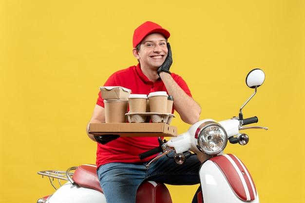 Vue de face du messager d'espoir souriant homme portant un chemisier rouge et des gants de chapeau en masque médical délivrant l'ordre assis sur des commandes de maintien de scooter