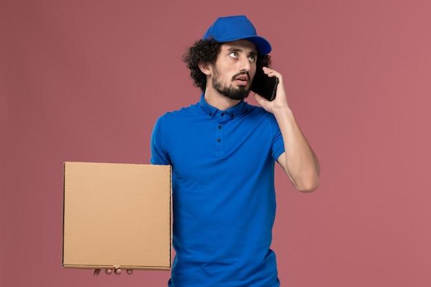 Vue de face du messager masculin en chapeau uniforme bleu avec boîte de nourriture sur ses mains en parlant au téléphone sur le mur rose clair