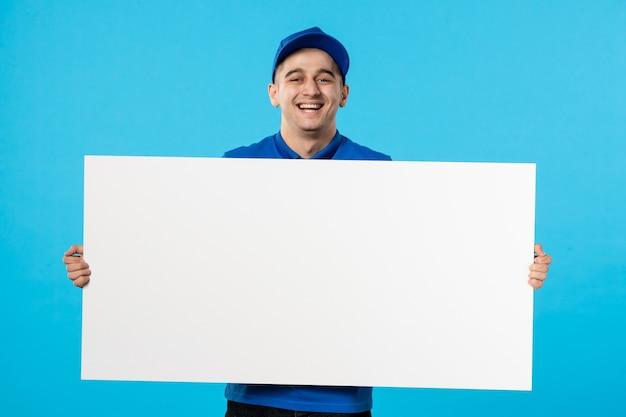 Vue de face du messager masculin en uniforme bleu avec un bureau uni blanc sur bleu