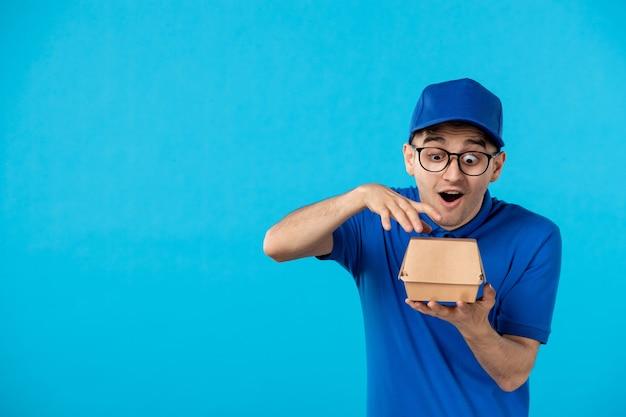 Vue de face du messager masculin en uniforme bleu avec peu de paquet de nourriture sur bleu