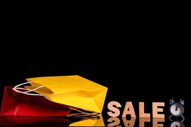 Vue de face du mot vente et sac avec fond noir