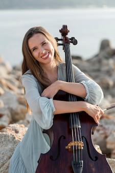 Vue de face du musicien féminin smiley avec violoncelle