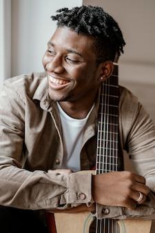 Vue de face du musicien masculin beau smiley à la maison posant avec guitare