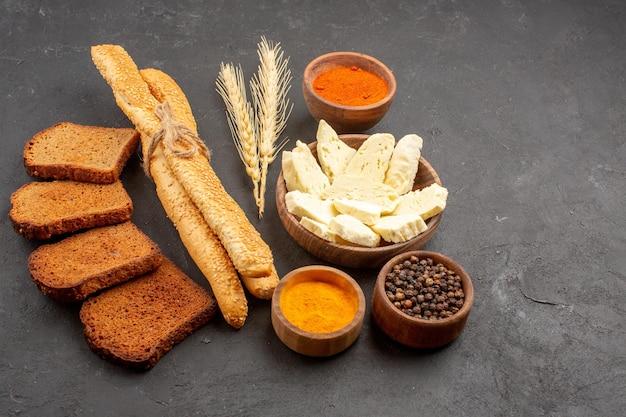 Vue de face du pain frais avec du fromage blanc et des assaisonnements sur un espace sombre