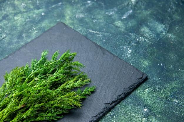 Vue de face du paquet d'aneth frais sur une planche à découper noire sur le côté droit sur fond de couleurs de mélange noir vert avec espace libre