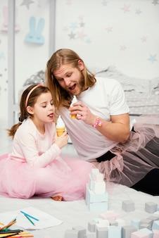 Vue de face du père et de la fille en jupes tutu manger des glaces