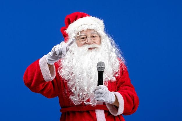 Vue de face du père noël avec un costume rouge et une barbe blanche tenant un micro sur les vacances de neige bleue couleur de noël nouvel an