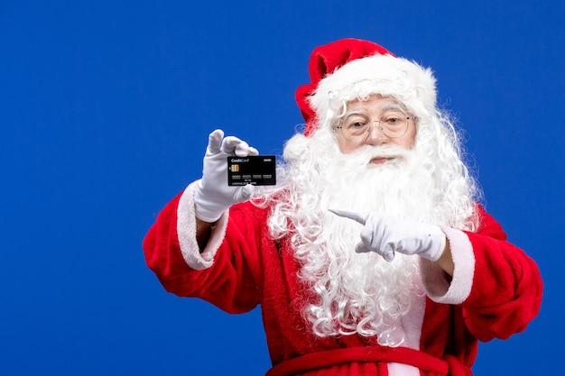 Vue de face du père noël en costume rouge tenant une carte bancaire noire sur les vacances de couleur bleue présente noël