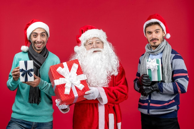 Vue de face du père noël avec deux hommes tenant des cadeaux sur le cadeau rouge émotion noël nouvel an rouge
