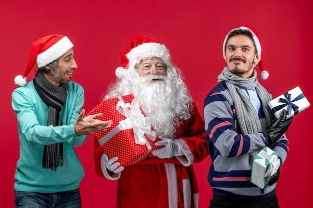 Vue de face du père noël avec deux hommes tenant des cadeaux sur le rouge rouge émotion cadeau du nouvel an noël