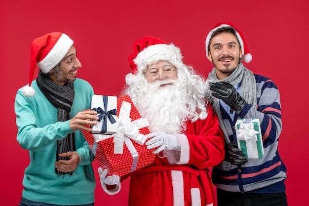 Vue de face du père noël avec deux hommes tenant des cadeaux sur rouge rouge nouvel an cadeau émotion noël