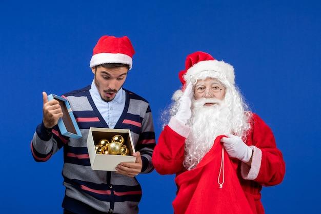 Vue de face du père noël donnant un cadeau à un jeune homme sur une émotion de nouvel an des vacances de noël bleu