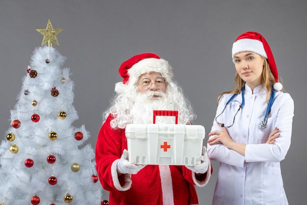 Vue de face du père noël avec une femme médecin qui lui a donné une trousse de premiers soins sur le mur gris