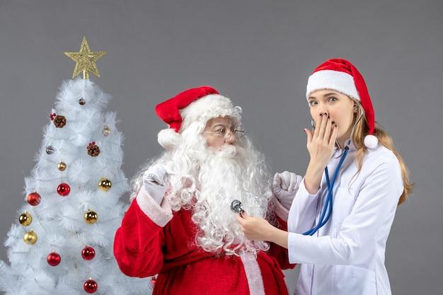 Vue de face du père noël avec femme médecin qui vérifie son état de santé sur un mur gris