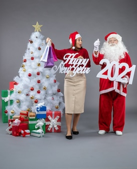 Vue de face du père noël avec femme tenant et bonne année shopping bagss sur le mur gris