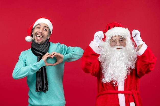 Vue de face du père noël avec un homme se sentant heureux sur le rouge présent vacances noël émotion nouvel an